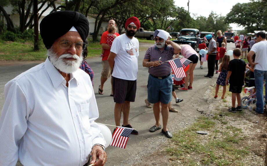 Shangara Singh Sandhu (left) looks around July 4, 2014 after he and other members of the Sikh Dharamsal congregation complete the parade route of the 17th annual HIlls & Dales Neighborhood Association Fourth of July parade. The parade which lasted about a quarter of a mile had over 100 people participate while walking the two long block of Shady Hollow Lane off of Babcock Road. Photo: Cynthia Esparza, For The San Antonio Express-News / For the San Antonio Express-News