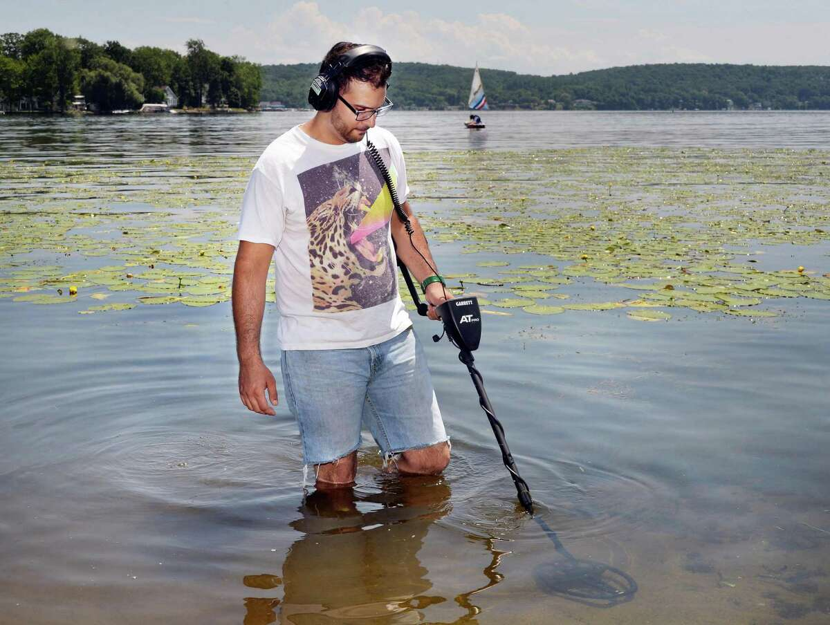 Steve Bell, a metal detector enthusiast who covers Saratoga and Lake George area for ringfinders.com, wades through Saratoga Lake using his metal detector Thursday, July 3, 2014, in Saratoga Springs, N.Y. (John Carl D'Annibale / Times Union)
