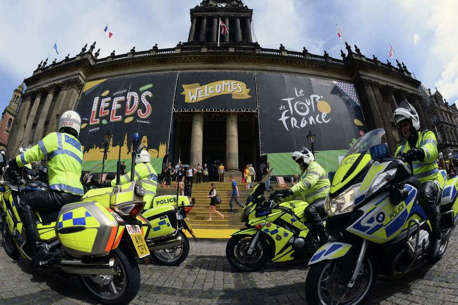British policemen working security ride past the city hall of Leeds in northern England before the start of the 101st Tour de France. Photo: LIONEL BONAVENTURE, Staff / AFP