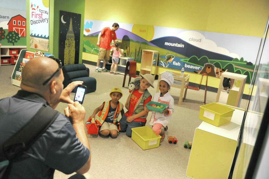 Antonio Rodriguez, left, of Albany takes a picture of his son Jair Rodroguez, 8, center of the group, with his friends in a recently renovated part of Discovery Place at the New York State Museum on Thursday July 3, 2014 in Albany, N.Y. (Michael P. Farrell/Times Union) Photo: Michael P. Farrell / 00027617A