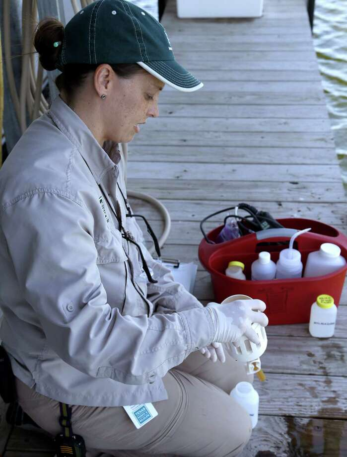 Monica McGarrity, a Texas Parks and Wildlife Department aquatic invasive species biologist, collects water samples from Lake Conroe. Photo: Pat Sullivan, STF / AP
