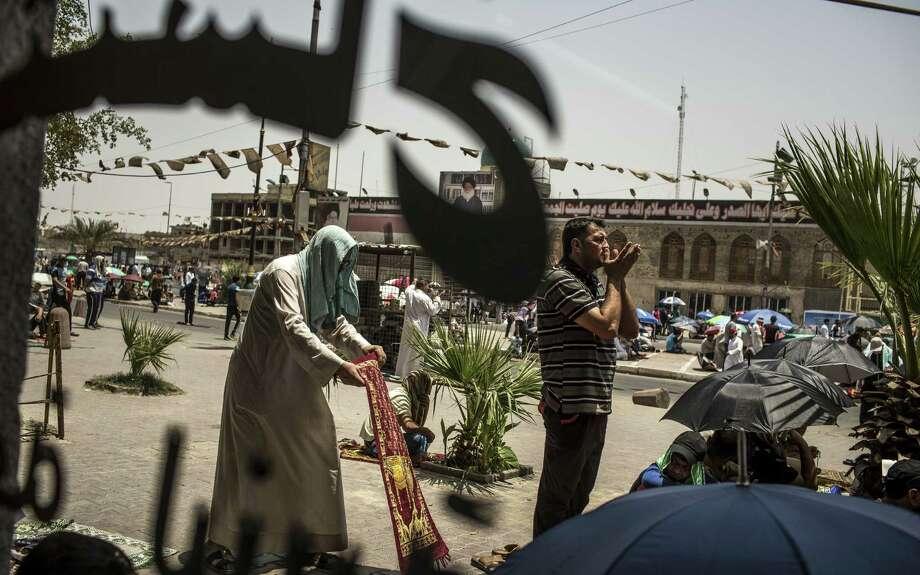Men participate in Friday prayers near an office of Shiite leader Muqtada al-Sadr in Sadr City area of Baghdad. Photo: Bryan Denton / New York Times / NYTNS