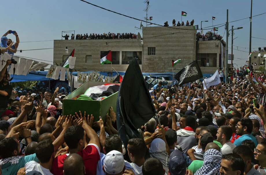 The body of Palestinian teenager Mohammed Abu Khdeir, wrapped in a Palestinian flag and traditional headscarf, is carried during his funeral in Jerusalem. Photo: Rina Castelnuovo / New York Times / NYTNS