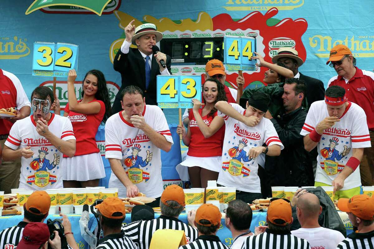 From left to right, Tim Janus, Joey Chestnut, Matt Stonie, and Erik Denmark compete during the Nathan's Famous Fourth of July International Hot Dog Eating contest at Coney Island, Friday, July 4, 2014, in New York. Chestnut won his eighth contest by finishing 61 hotdogs and buns. (AP Photo/John Minchillo) ORG XMIT: NYJM101