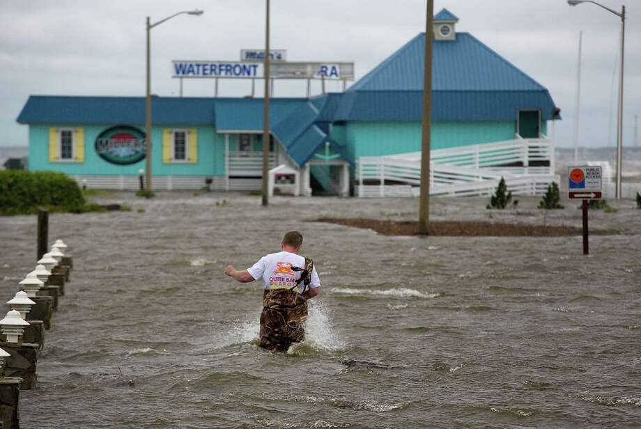 Bryan Wilson, owner of a waterfront restaurant, braves floodwaters to check the damage to his property as wind from Hurricane Arthur pushes water to his parking lot in Nags Head, N.C. Photo: Hyunsoo Leo Kim / Associated Press / The Virginian-Pilot