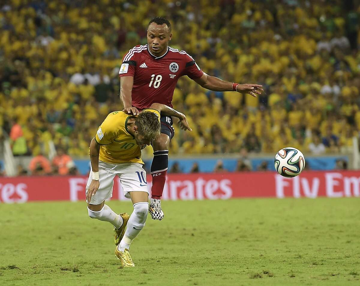 Brazil's Neymar is fouled by Colombia's Juan Zuniga during the World Cup quarterfinal soccer match between Brazil and Colombia at the Arena Castelao in Fortaleza, Brazil, Friday, July 4, 2014. (AP Photo/Manu Fernandez)