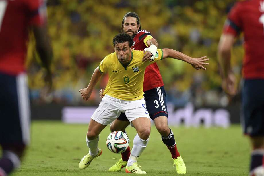 Fred, here shielding Colombia's Mario Alberto Yepes from the ball, is apparently not a fan favorite in Brazil. A poll rates him as the team's worst player. Photo: FABRICE COFFRINI, Staff / AFP
