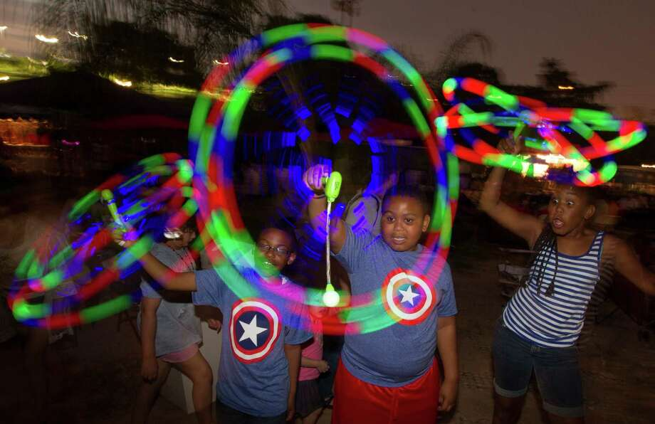 Lance Tanner, 9, (left) his cousins Kortez, 8, and Kelsey Winslow, 9, light up the sky with a spinning toy during the Freedom Over Texas Fourth of July celebration at Eleanor Tinsley Park on Friday, July 4, 2014, in Houston. Photo: J. Patric Schneider, For The Chronicle / © 2014 Houston Chronicle