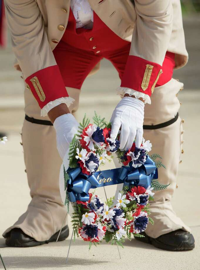 Joe Zavala places a memorial wreath during an Independence Day ceremony on Friday, July 4, 2014, at Fort Sam Houston National Cemetery in San Antonio. (Darren Abate/For the Express-News) Photo: Photo By Darren Abate/Express-News / DA Media, LLC