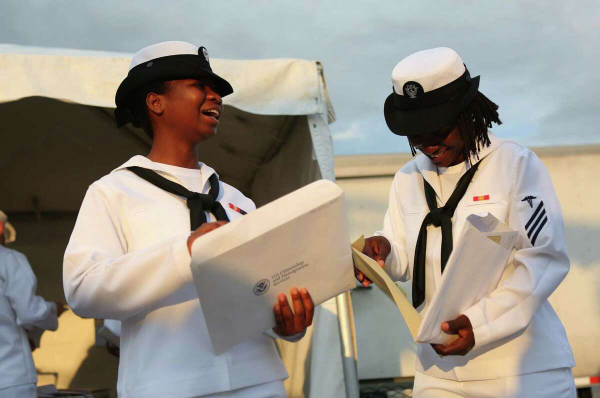 U.S. Navy Seaman Benedicta Ayikpah (left), a native of Ghana, and Seaman Ifeoma Odimegwu, a native of Nigeria, look over citizenship documents after the naturalization ceremony.