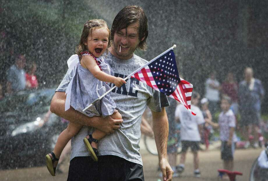 John David Dowdle holds his daughter Blakely Dowdle as she laughs while being sprayed with water by the Germantown Fire Department in Tennessee. Photo: Yalonda M. James / Commercial Appeal (Memphis) / The Commercial Appeal