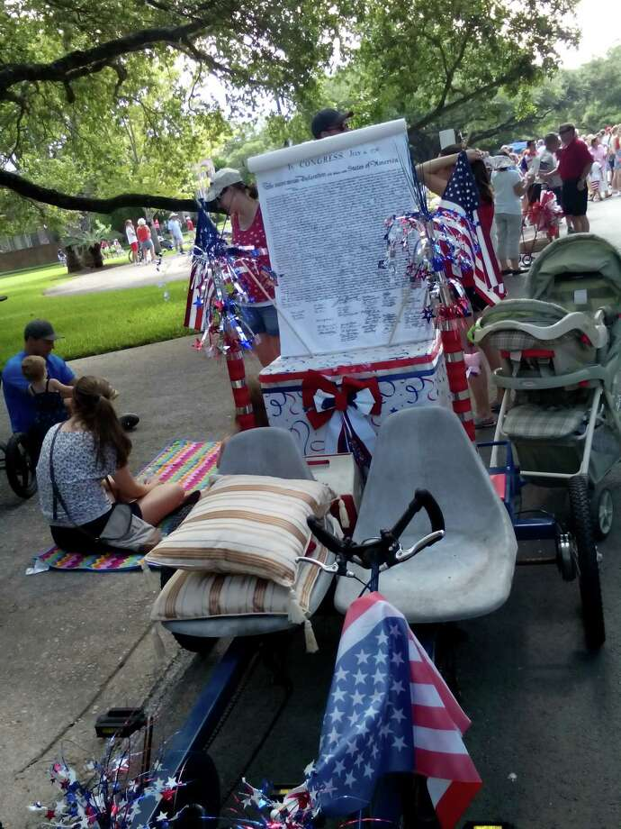 Participants in Terrell Hills' Fourth of July parade Friday rode vintage cars and unique cycles such as this one carrying the Declaration of Independence. Photo: Edmond Ortiz / Alamo Heights Wee