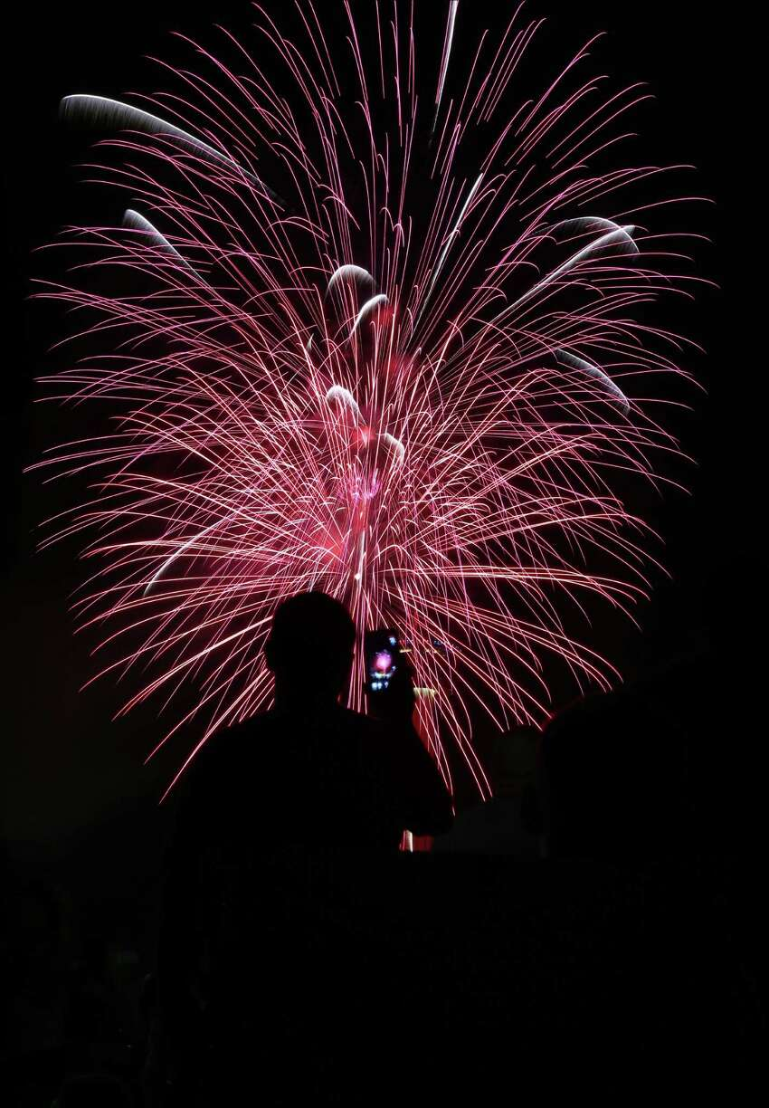 A man attending the Stars and Stripes on Thursday, July 4, 2014, at the Alamodome in San Antonio, records fireworks being set off from HemisFair Park.