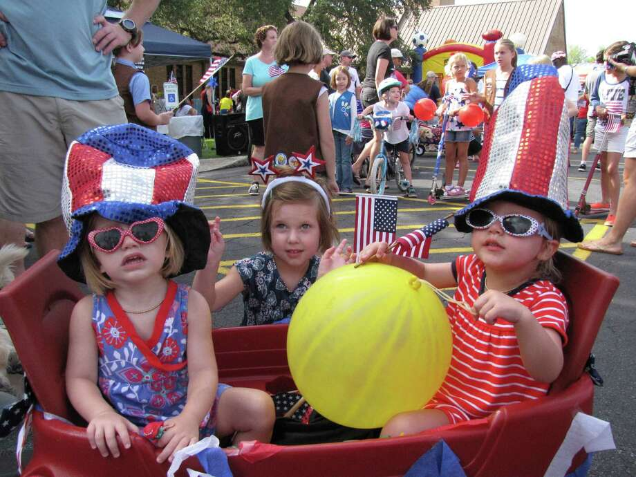 From left, Annie and Emmy Myers, and Claire Toppin prepare to ride in the Oak Park/Northwood Neighborhood Association's Fourth of July parade held Friday. Photo: Edmond Ortiz / Alamo Heights Wee