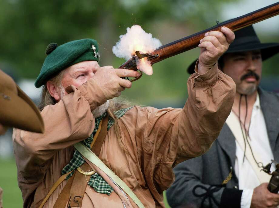 Pennsylvania Militia re-enactor Randy Pike fires his musket during an Independence Day ceremony on Friday, July 4, 2014, at Fort Sam Houston National Cemetery in San Antonio. (Darren Abate/For the Express-News) Photo: Darren Abate, Darren Abate/Express-News / DA Media, LLC