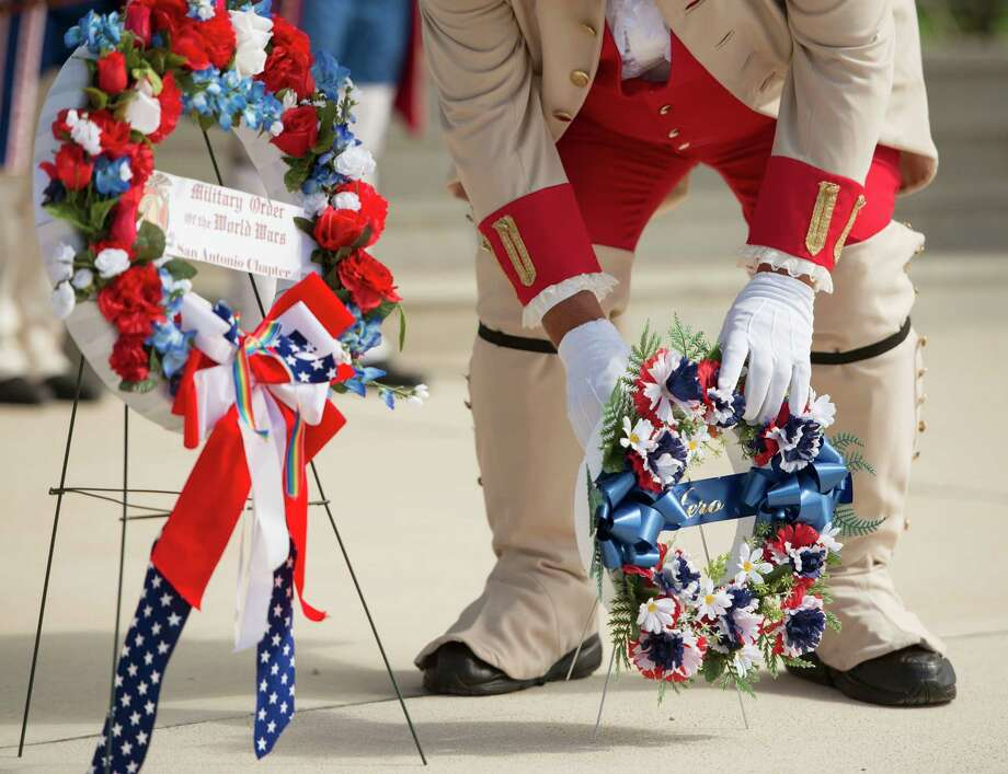 Joe Zavala places a memorial wreath during an Independence Day ceremony on Friday, July 4, 2014, at Fort Sam Houston National Cemetery in San Antonio. (Darren Abate/For the Express-News) Photo: Darren Abate, Darren Abate/Express-News / DA Media, LLC