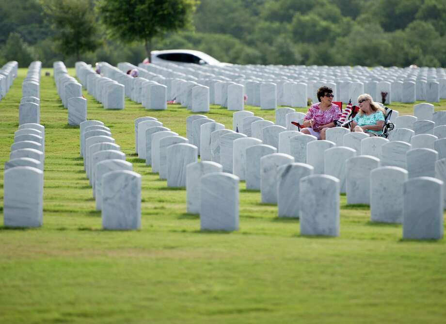 Two women sit amongst the head stones during an Independence Day ceremony on Friday, July 4, 2014, at Fort Sam Houston National Cemetery in San Antonio. (Darren Abate/For the Express-News) Photo: Darren Abate, Darren Abate/Express-News / DA Media, LLC