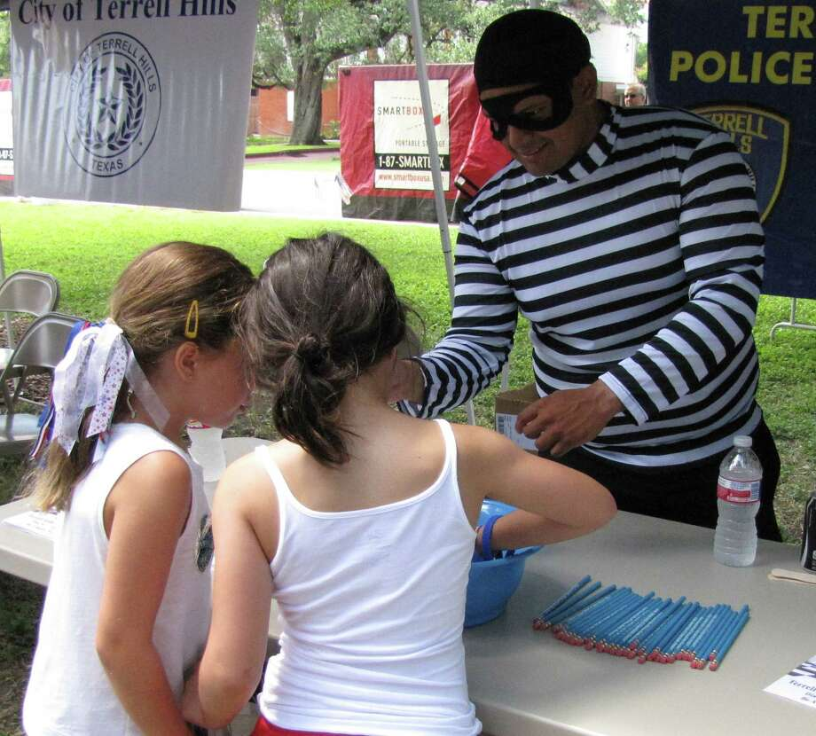 """Bobby the Burglar,"" aka Terrell Hills Police Officer Guadalupe Navarro, talks with young attendees of the city's Independence Day parade and picnic Friday. ""Bobby"" is the local police department's new crime-fighting educational mascot. Photo: Edmond Ortiz / Alamo Heights Wee"