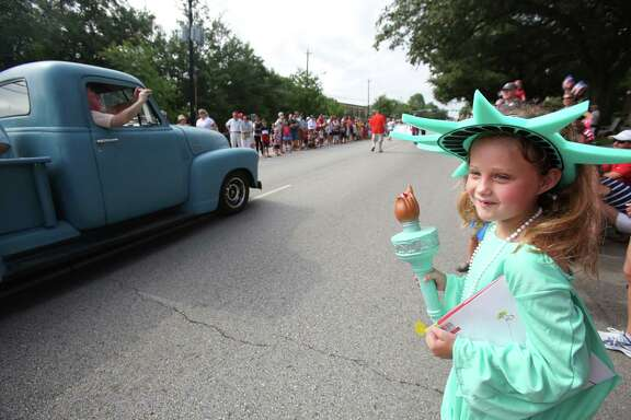 "Amanda Lee Huttenback, 8, dressed as the ""Statue of Kid-berty,"" enjoys the Bellaire Fourth of July Parade with hundreds of others."