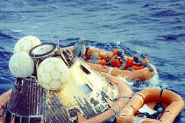 """ap11-KSC-69PC-467HR - """"Apollo 11 astronauts, plus Navy diver, in raft after splashdown - wearing biological isolation garments. July 24, 1969"""""""