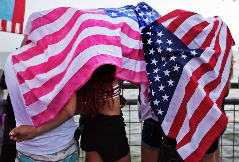 Kemah Boardwalk guests take shelter from the drizzle while they wait for the Independence Dayfireworks, at Galveston Bay, Friday, July 4, 2014, in Kemah. Photo: Marie D. De Jesus, Houston Chronicle / © 2014 Houston Chronicle