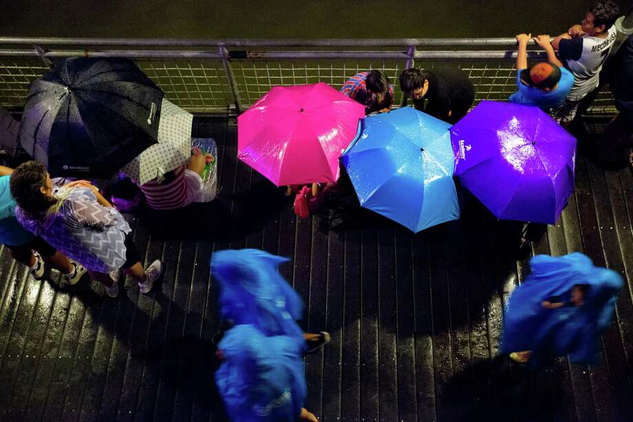 Kemah Boardwalk guests take shelter from the drizzle while they wait for the Independence Day fireworks, at Galveston Bay, Friday, July 4, 2014, in Kemah. Photo: Marie D. De Jesus, Houston Chronicle / © 2014 Houston Chronicle