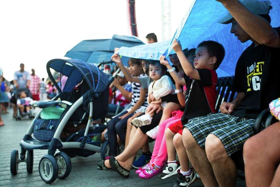 An entire family takes shelter from the rain during the Independence Day festivities at Kemah Boardwalk, as they  wait of the fireworks over Galveston Bay, Friday, July 4, 2014, in Kemah. Photo: Marie D. De Jesus, Houston Chronicle / © 2014 Houston Chronicle
