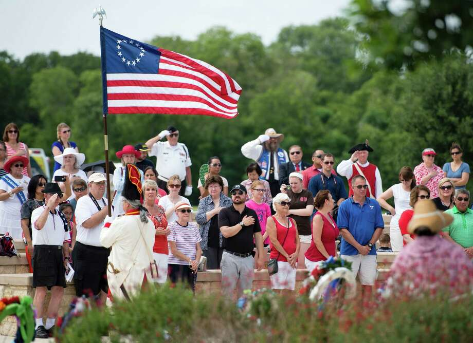 Spectators salute the retiring of the colors during an Independence Day ceremony on Friday, July 4, 2014, at Fort Sam Houston National Cemetery in San Antonio. (Darren Abate/For the Express-News) Photo: Darren Abate, Darren Abate/Express-News / DA Media, LLC