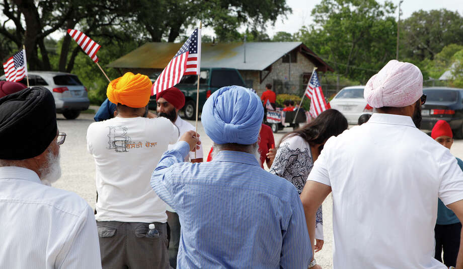 Members of the Sikh Dharamsal congregation hold up the flags they were carrying July 4, 2014 as they get to the end of the 17th annual HIlls & Dales Neighborhood Association Fourth of July parade. The parade which lasted about a quarter of a mile had over 100 people participate while walking the two long block of Shady Hollow Lane off of Babcock Road and ended at the neighborhood park with hot dogs, watermelon and lemonade. Photo: For The San Antonio Express-News / For the San Antonio Express-News