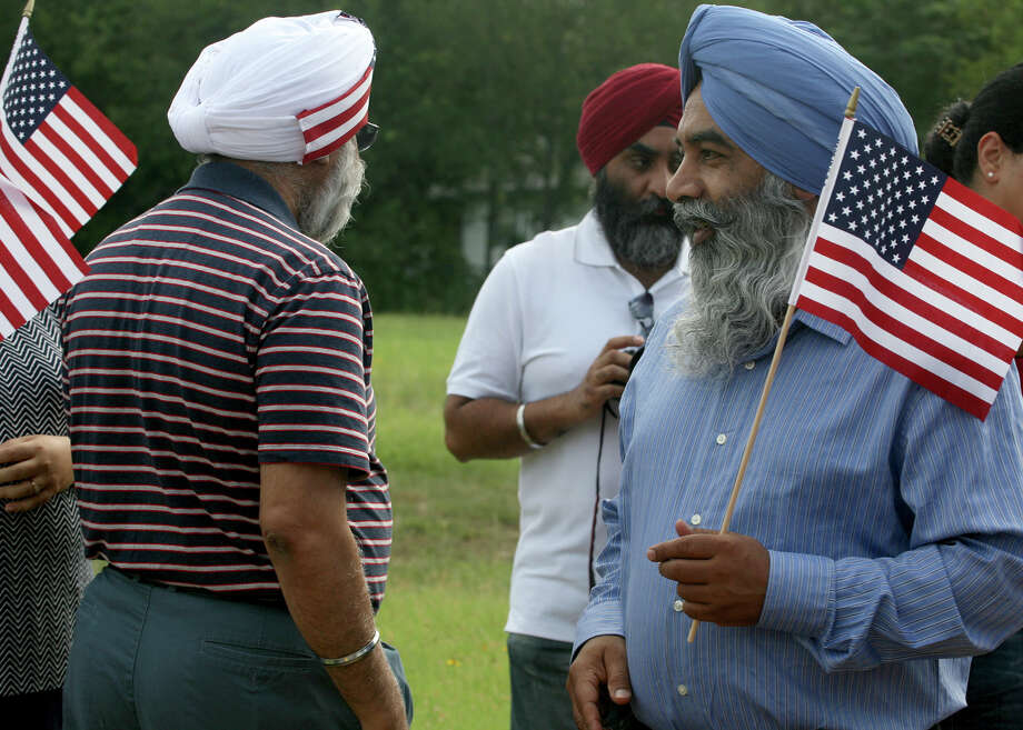 Jantinder Singh (right) walks around with his American flag July 4, 2014 as he prepares to participate in the 17th annual HIlls & Dales Neighborhood Association Fourth of July parade. Members of the Sikh Dharamsal congregation took part in the parade for the first time this year. Photo: For The San Antonio Express-News / For the San Antonio Express-News