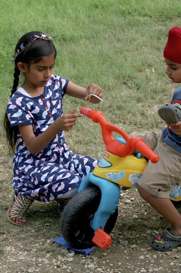 Bani Kaur, 7, helps decorate Kubbi Singh's, 3, tricycle July 4, 2014 as they and other members of the Sikh Dharamsal congregation prepare to participate for the first time in the 17th annual HIlls & Dales Neighborhood Association Fourth of July parade. Photo: For The San Antonio Express-News / For the San Antonio Express-News