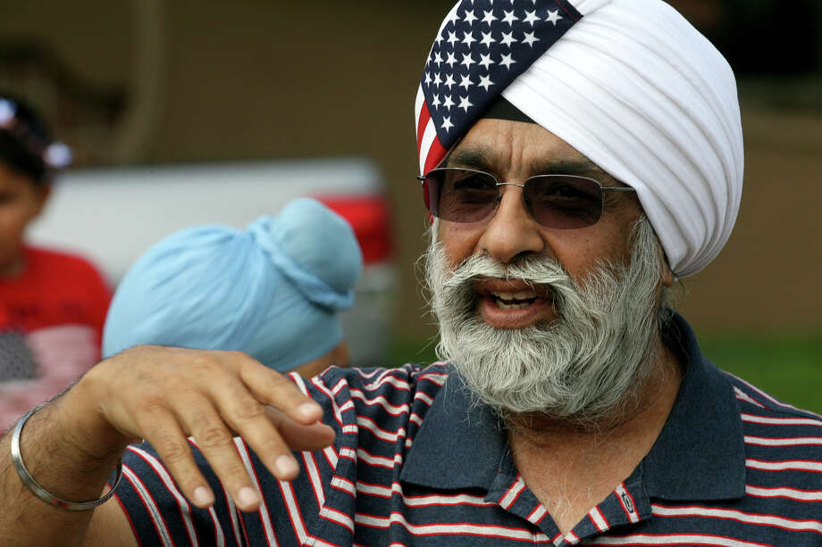 GP Singh, president of the new Sikh temple being built on Green Glen Drive, calls for members of the Sikh Dharamsal congregation to start lining up July 4, 2014 to paticipate in the 17th annual HIlls & Dales Neighborhood Association Fourth of July parade. This was the first time for the Sikh Dharamsal congregation members to participate in the parade which lasted about a quarter of a mile down two long blocks of Shady Hollow Lane off of Babcock Road. Photo: For The San Antonio Express-News / For the San Antonio Express-News