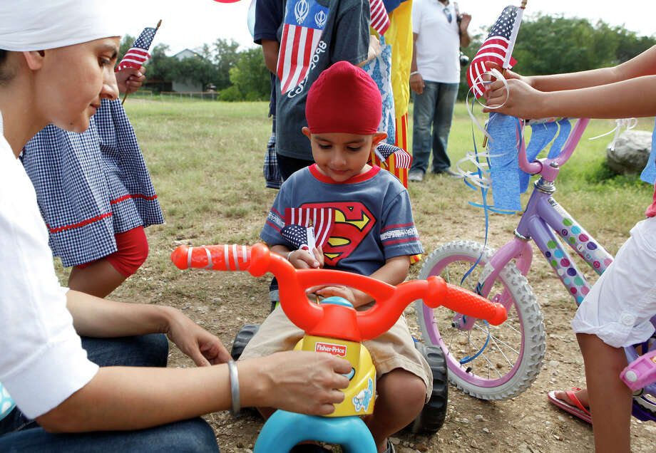 Harvil Kaur (left) helps her son, Kubbi Singh, 3, try to stick an American flag to his tricycle as they prepare to participate, along with other members of the Sikh Dharamsal congregation, for the first time July 4, 2014 in the 17th annual HIlls & Dales Neighborhood Association Fourth of July parade. Photo: For The San Antonio Express-News / For the San Antonio Express-News