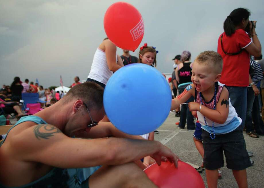 Ben Sahlberg, 1, right, hits his father, Adam Sahlberg, with a balloon during the Stars and Stripes over San Antonio event on Thursday, July 4, 2014, at the Alamodome in San Antonio. Photo: Timothy Tai, San Antonio Express-News / © 2014 San Antonio Express-News