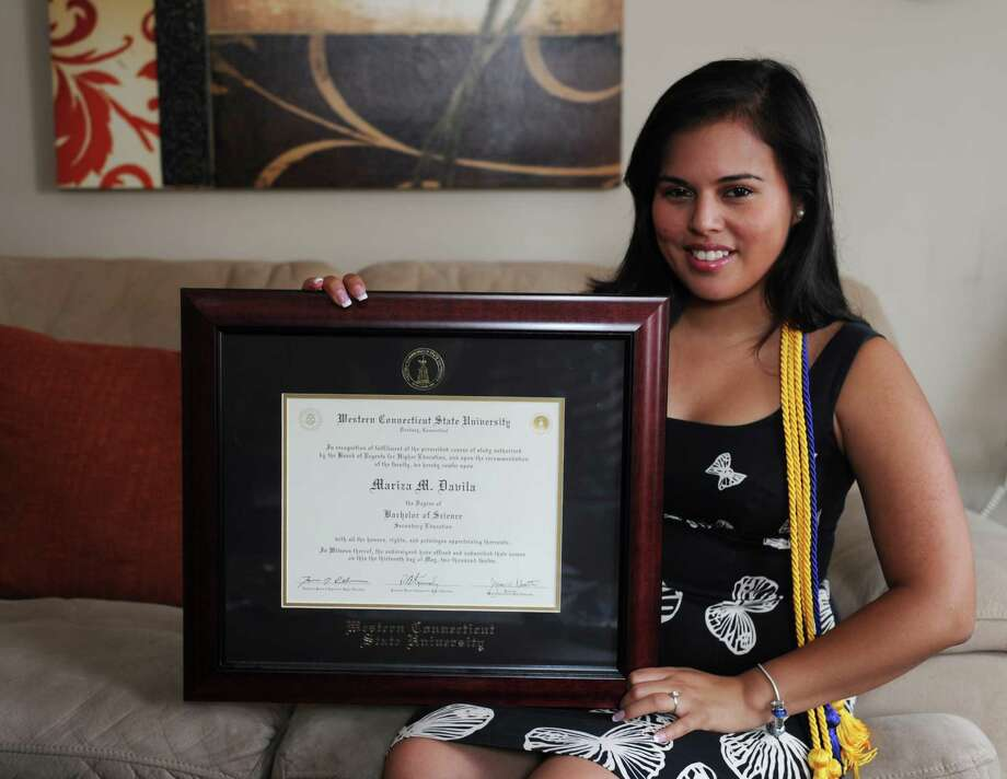 Mariza Davila, a Spanish teacher at Bethel High School, poses with her Western Connecticut State diploma inside her Danbury, Conn. home on Wednesday, June 25, 2014.  Davila is taking advantage of the benefits of the Deferred Action for Childhood Arrivals program, which states that certain people who immigrated to the United States as children and meet certain guidelines may request consideration of deferred action for a period of two years, subject to renewal. Photo: Tyler Sizemore / Co