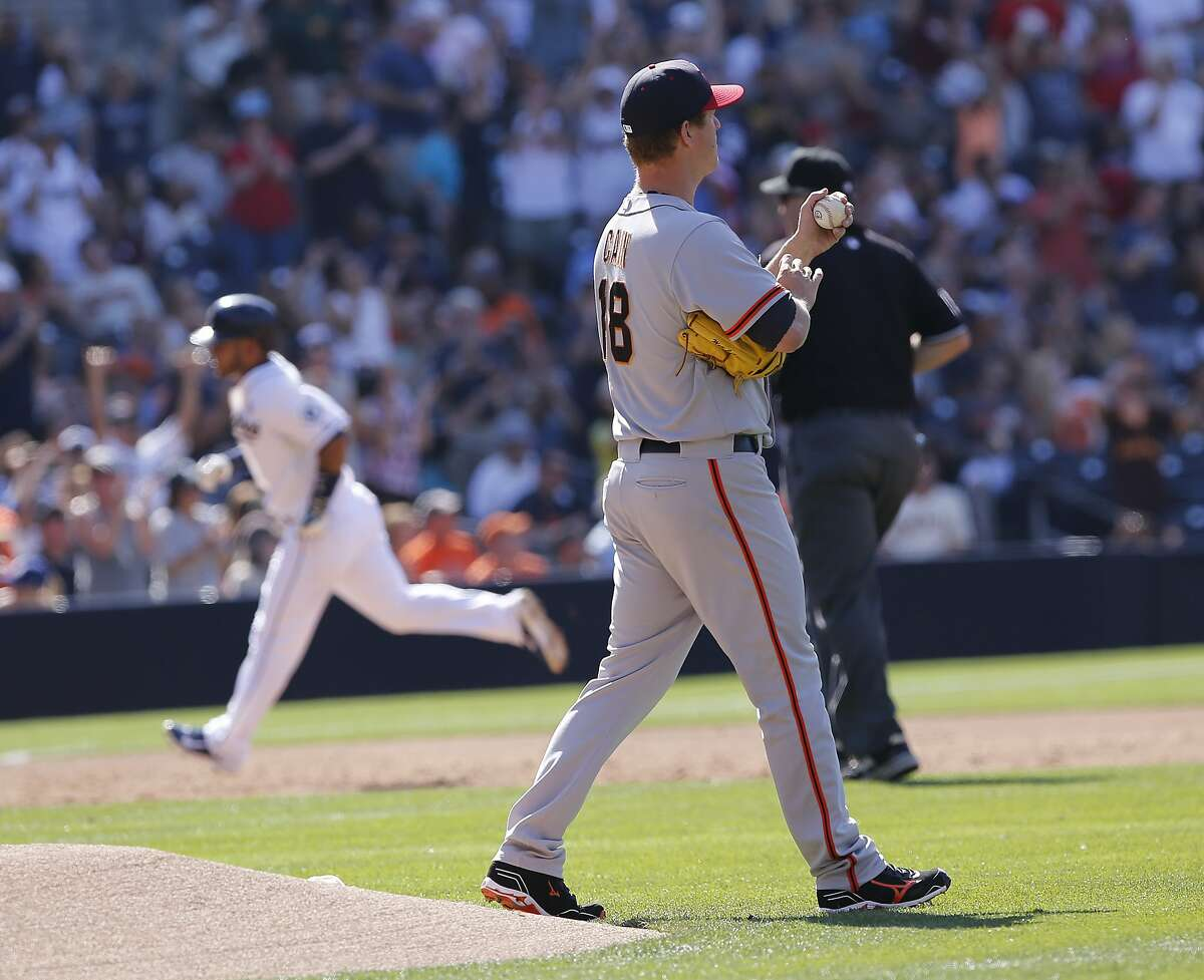 San Francisco Giants starting pitcher Matt Cain, foreground, walks off the mound as San Diego Padres' Alexi Amarista, back left, rounds the bases after hitting a home run in the third inning of a baseball game on Friday, July 4, 2014, in San Diego. (AP Photo/Don Boomer)