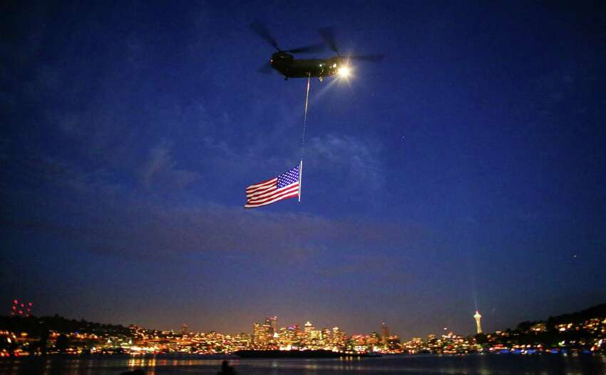 A Washington National Guard Chinook helicopter kicks off the ceremonies during the Seafair Summer Fourth at Gas Works Park. Tens of thousands of people packed the park during the annual firework display. Hundreds of thousands watched from surrounding neighborhoods. Photographed on Friday, July 4, 2014.