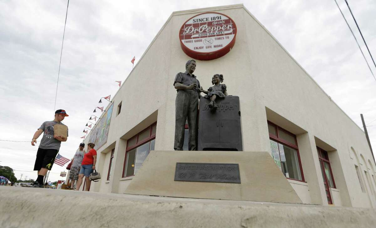 In this June 14, 2014 photo, visitors walk by the historic Dr. Pepper bottling plant in Dublin, Texas. The departure of Dr. Pepper two years ago was a blow to this small Central Texas town. For decades Dr. Pepper's oldest bottling plant drew tens of thousands of tourists a year.