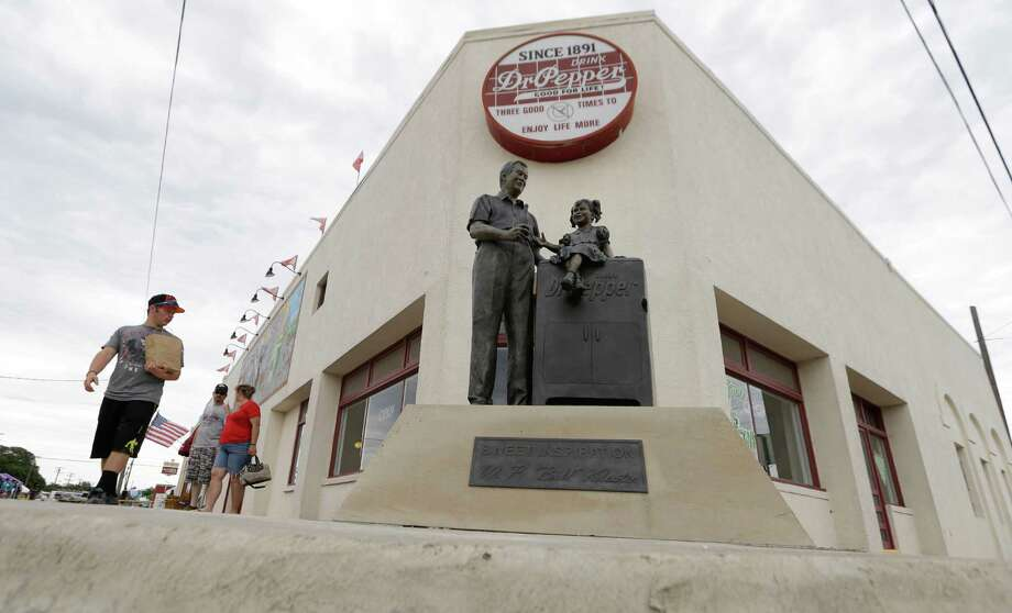 In this June 14, 2014 photo, visitors walk by the historic Dr. Pepper bottling plant in Dublin, Texas. The departure of Dr. Pepper two years ago was a blow to this small Central Texas town. For decades Dr. Pepper's oldest bottling plant drew tens of thousands of tourists a year. Photo: LM Otero, AP / AP