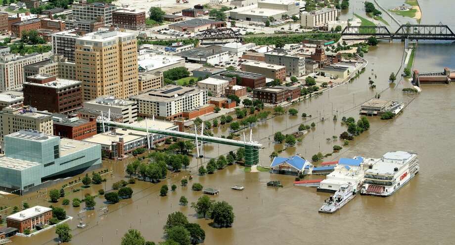 This Thursday, July 3, 2014 aerial photo shows flooding along River Drive in Davenport, Iowa as the Mississippi River approaches the crest. The National Weather Service reported that the Mississippi River crested in Davenport at 20.89 feet — well above flood stage of 15 feet but nearly two feet below the record set in 1993. (AP Photo/The Quad City Times, John Schultz) MAGAZINES OUT; TV OUT; NO SALES Photo: John Schultz, AP
