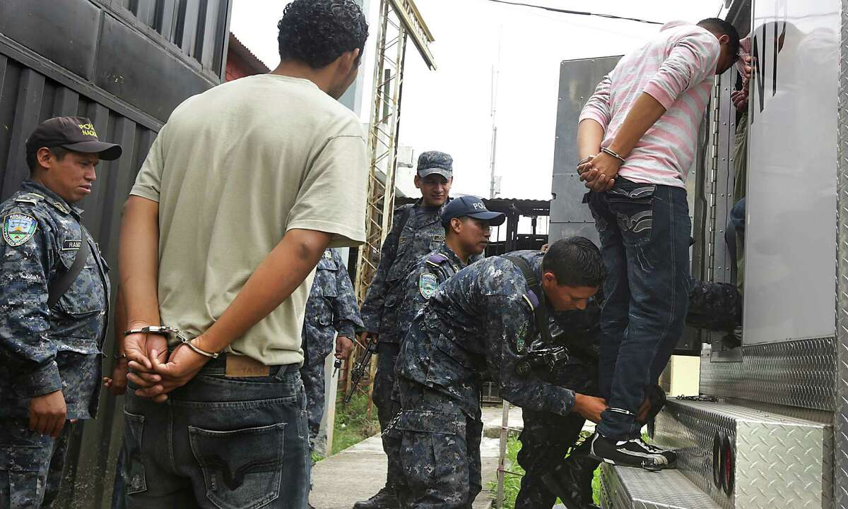 Inmates are cuffed by National Police before being transported from the National Penitentiary in Tegucigalpa, Honduras, to a court hearing. Violence in the Central American country is a main reason so many immigrants are going to the U.S. Thursday, July 3, 2014.