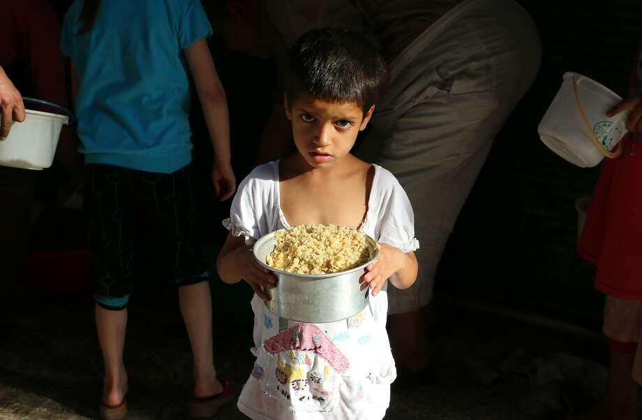 A Syrian boy carries a food ration distributed by volunteers to poor families during the Muslim holy fasting month of Ramadan, in a rebel-held area in the northern city of Aleppo on July 5, 2014. More than 162,000 people have been killed in Syria since the uprising against Assad's rule erupted in March 2011. AFP PHOTO/BARAA AL-HALABIBARAA AL-HALABI/AFP/Getty Images Photo: Baraa Al-halabi, AFP/Getty Images