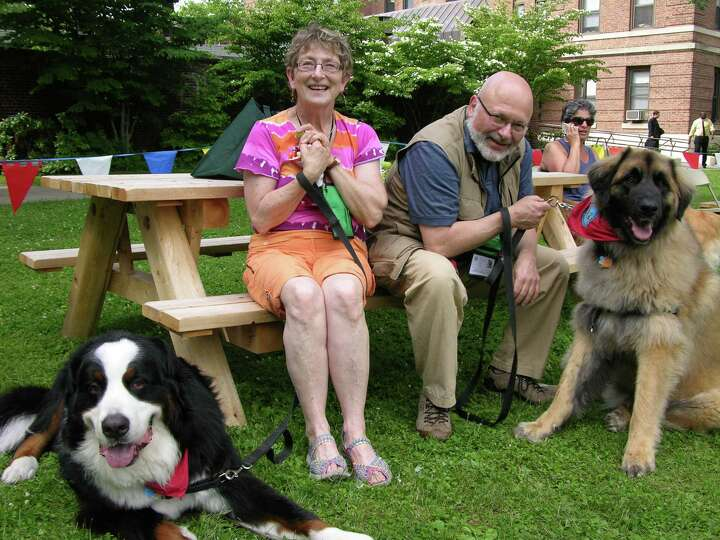 Owners Happy and Harvey Scherer sit with their two therapy dogs, Oliver and Merlin, while waiting to