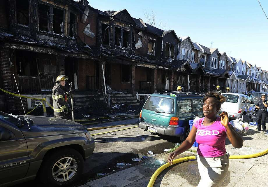 A woman cries as she walks past firefighters working on at least 10 row houses that were burned. Photo: Michael Perez, Associated Press
