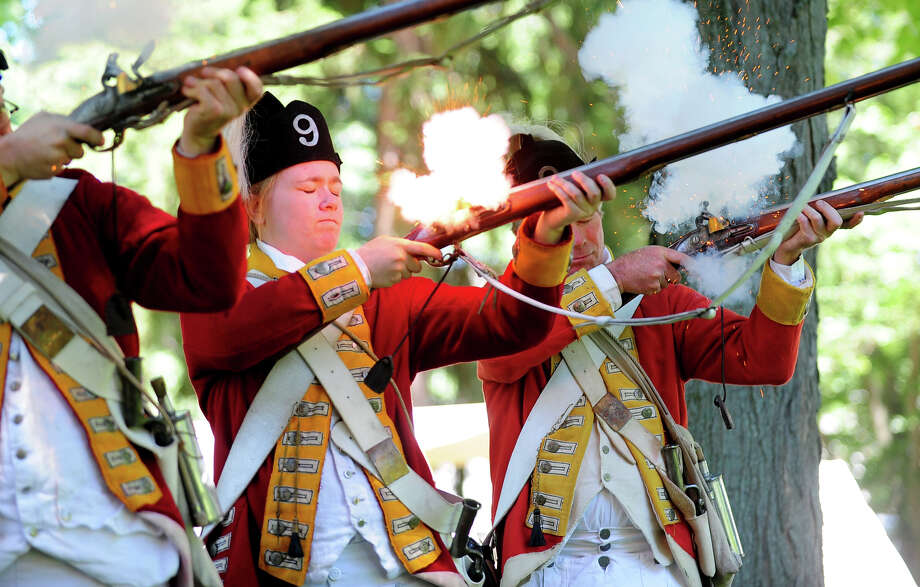 "Sarah Murphy, with the British Seventh Company of the Ninth Regiment of Foot, fires a replica musket rife with her fellow Revolutionary War re-enactors, during Family Fun Fest held on the Town Hall Green and the Fairfield Museum and History Center in Fairfield, Conn. on Saturday July 5, 2014. The festival featured a full slate of musical entertainment, artisan fair, and games and activities for children. Also, Revolutionary War British soldier re-enactors were encamped on the premises, wearing the traditional ""red coat"" uniforms as well as firing replica period musket rifles. Photo: Christian Abraham / Connecticut Post"