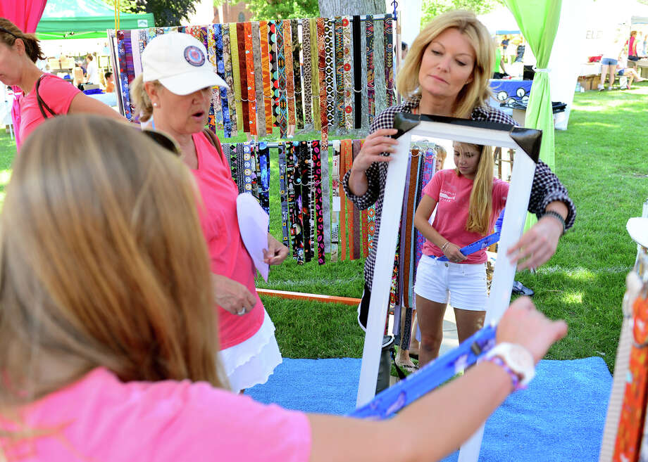 "Molly Broah, of Fairfield, tries on a belt as Sandra Oles, holds up a mirror for her, during Family Fun Fest held on the Town Hall Green and the Fairfield Museum and History Center in Fairfield, Conn. on Saturday July 5, 2014. The festival featured a full slate of musical entertainment, artisan fair, and games and activities for children. Also, Revolutionary War British soldier re-enactors were encamped on the premises, wearing the traditional ""red coat"" uniforms as well as firing replica period musket rifles. Photo: Christian Abraham / Connecticut Post"