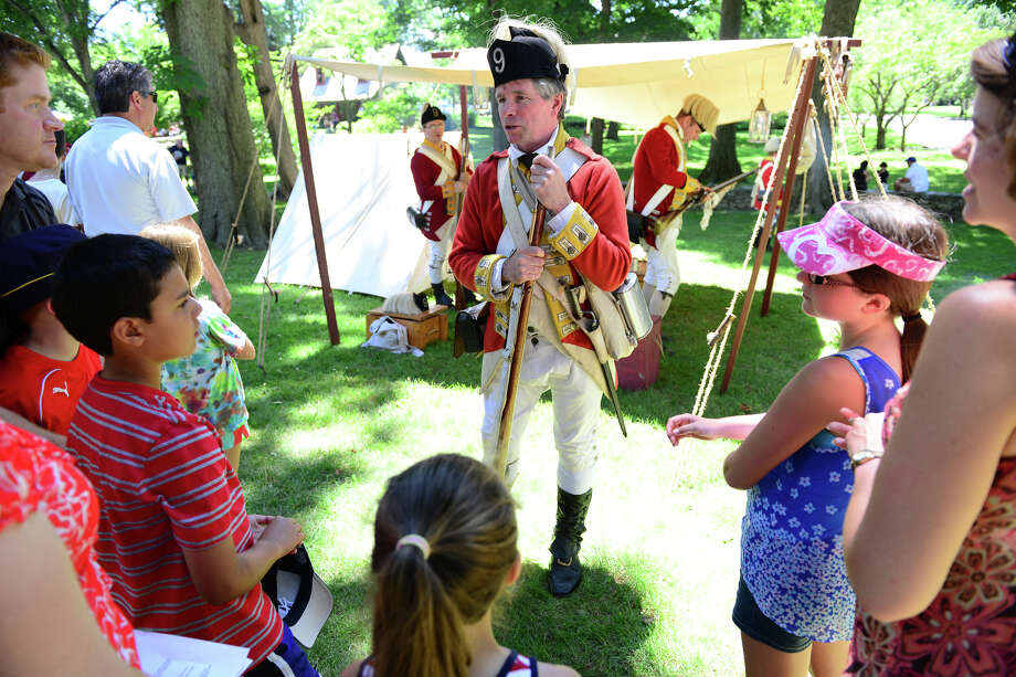"Revolutionary War re-enactor Jim Murphy, with the British Seventh Company of the Ninth Regiment of Foot, answers questions during Family Fun Fest held on the Town Hall Green and the Fairfield Museum and History Center in Fairfield, Conn. on Saturday July 5, 2014. The festival featured a full slate of musical entertainment, artisan fair, and games and activities for children. Also, Revolutionary War British soldier re-enactors were encamped on the premises, wearing the traditional ""red coat"" uniforms as well as firing replica period musket rifles. Photo: Christian Abraham / Connecticut Post"