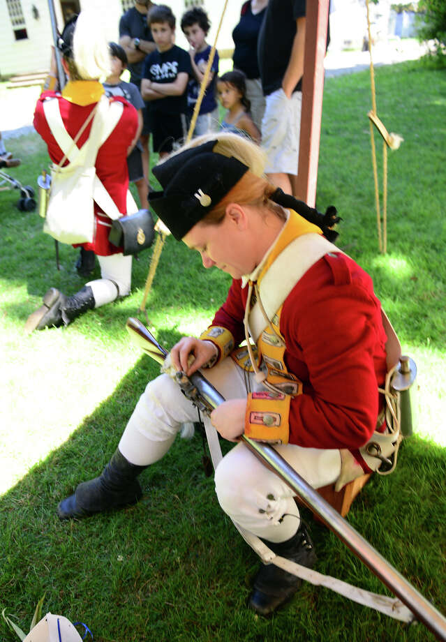 Sarah Murphy, a Revolutionary War re-enactor with the British Seventh Company of the Ninth Regiment of Foot, cleans her musket rifle during Family Fun Fest held on the Town Hall Green and the Fairfield Museum and History Center in Fairfield, Conn. on Saturday July 5, 2014. The festival featured a full slate of musical entertainment, artisan fair, and games and activities for children. Photo: Christian Abraham / Connecticut Post