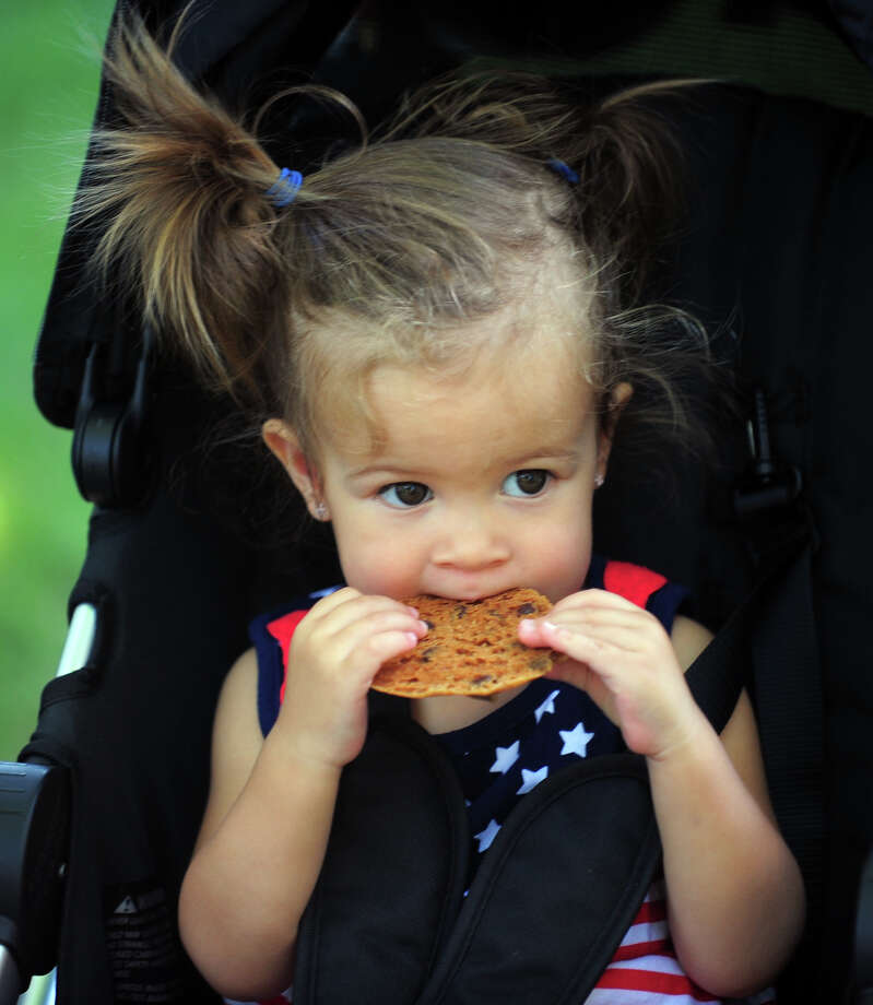 "Isabella Hegedus, 1, of Fairfield, enjoys a cookie, during Family Fun Fest held on the Town Hall Green and the Fairfield Museum and History Center in Fairfield, Conn. on Saturday July 5, 2014. The festival featured a full slate of musical entertainment, artisan fair, and games and activities for children. Also, Revolutionary War British soldier re-enactors were encamped on the premises, wearing the traditional ""red coat"" uniforms as well as firing replica period musket rifles. Photo: Christian Abraham / Connecticut Post"