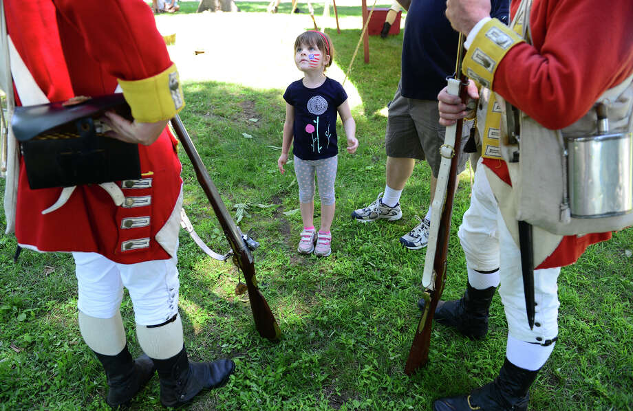 Richard Young, a re-enactor with the Seventh Company of the Ninth Regiment of Foot, left, explains how his musket works to Kaitlyn Derfinyak, 4, of Stamford, during Family Fun Fest held on the Town Hall Green and the Fairfield Museum and History Center in Fairfield, Conn. on Saturday July 5, 2014. The festival featured a full slate of musical entertainment, artisan fair, and games and activities for children. Photo: Christian Abraham / Connecticut Post
